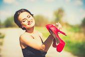 stock photo of barefoot  - Barefoot brunette girl outdoor with red high heels in her hands - JPG