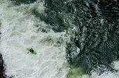 image of kayak  - A green kayaker paddles through rushing white water - JPG