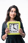 pic of late 20s  - Pensive businesswoman holding clock isolated on a white background and looking away - JPG