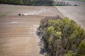 pic of cultivator-harrow  - Aerial view of the the tractor harrowing the large brown field in spring season - JPG