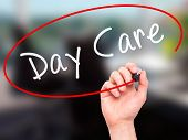 stock photo of day care center  - Man Hand writing Day Care with marker on transparent wipe board - JPG