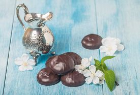 image of milkman  - small chocolate-covered cream cakes on blue wooden background with white flowers and milkman ** Note: Shallow depth of field - JPG