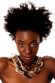 stock photo of afro hair  - Beautiful face of an African tribal woman with Afro curly hair bare shoulders and smooth brown skin wearing Earth - JPG