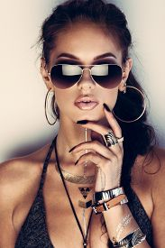 stock photo of flashing  - Glamorous young woman with flash tattoos in sunglasses - JPG