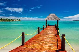 stock photo of jetties  - Short red wooden jetty extending to tropical ocean on Fiji Island - JPG