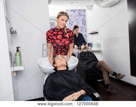 Hairstylist Washing Customer's Hair In Beauty Salon