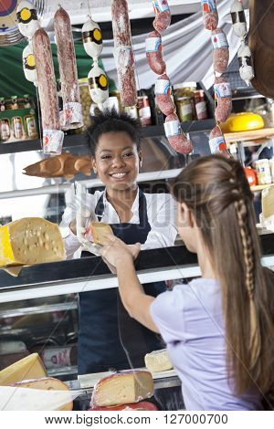 Happy Saleswoman Selling Cheese To Female Customer