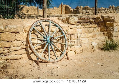 Old wooden wheel with an iron rim leaning up against a ancient stone wall
