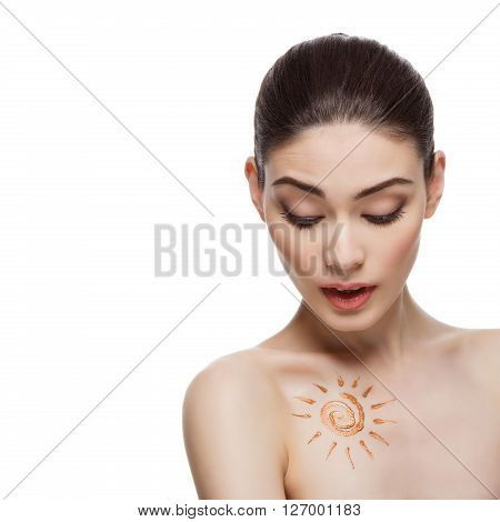 Beautiful young woman with tan bronzer cream sun shape drawing on chest. Isolated over white background. Copy space. Square composition.