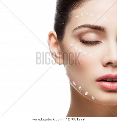 Beautiful young woman with moisturizing cream dots on face. Isolated over white background. Copy space. Square composition.