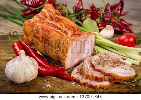chopped bacon with spices and vegetables on wooden cutting board