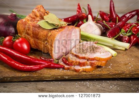 chopped bacon with spices and vegetables on woden cutting board