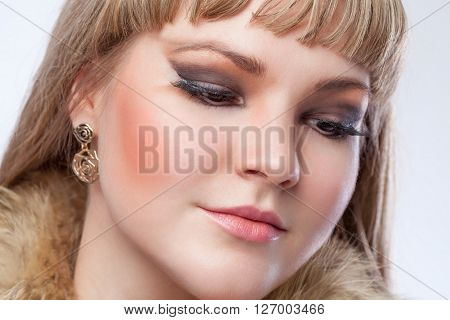 Face of a beautiful blonde girl close-up. Sad girl with downcast eyes. Beauty.