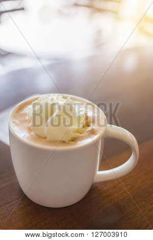 Close focus on hot mocha coffee with milk whip cream in white cup on wooden table and bright light ** Note: Shallow depth of field