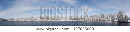 Seven photo panorama of a beautiful snow covered trees along a lake with a nice blue sky with soft white clouds.