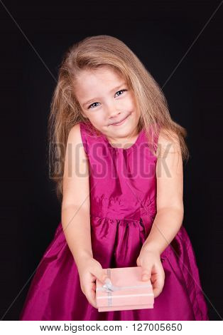 Portrait of a joyful little girl in a pink dress with a gift in her hands on a black background in the studio