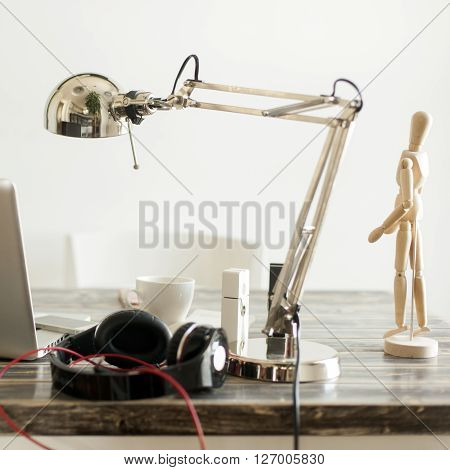 Artistic working desk, lamp, laptop, mobile phone, headphones, coffee, clamps and cables