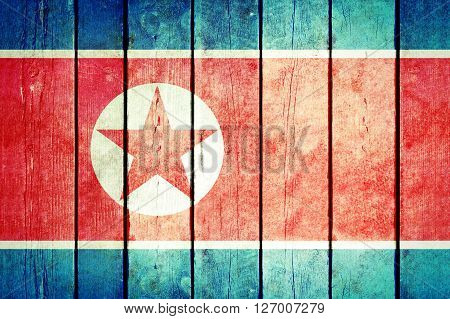 North Korea wooden grunge flag. North Korea flag painted on the old wooden planks. Vintage retro picture from my collection of flags.