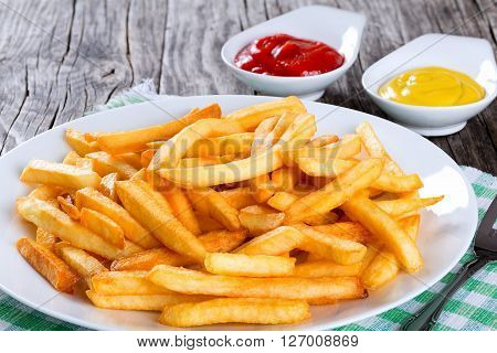 Tasty french fries on a white plate with mustard and tomato sauce in a gravy boat on wooden table background close-up view from above