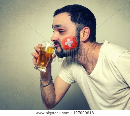 funny bearded sport fan of Switzerland drinking beer