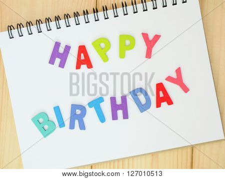Wooden word spell Happy Birthday on notebook with wood background