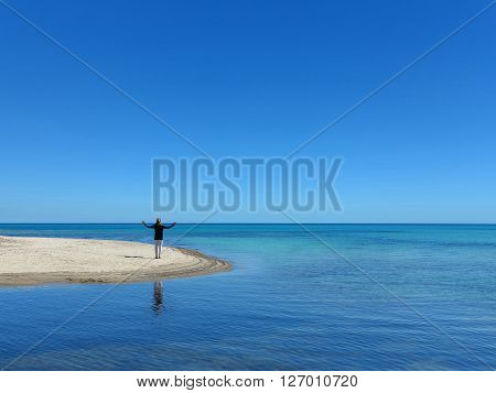 woman on sandbank spreading her arms and welcoming the sea