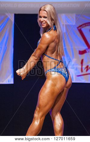 MAASTRICHT THE NETHERLANDS - OCTOBER 25 2015: Female fitness model Kinga Golebiewska flexes her muscles and shows her best physique in a back pose on stage at the World Grandprix Bodybuilding and Fitness of the WBBF-WFF on October 25 2015 at the MECC