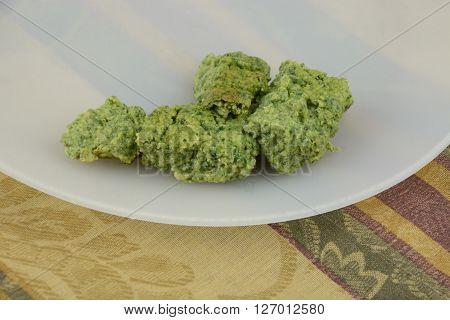 Spinach souffle on white plate on tablecloth