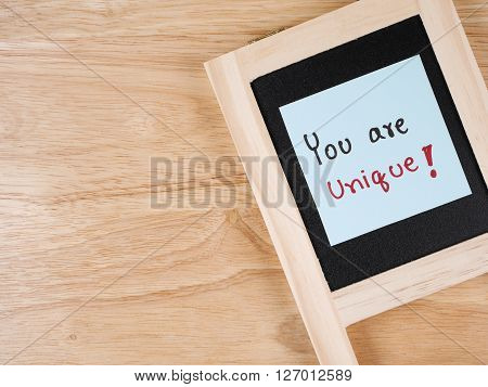Handwriting word You Are Unique on color note paper and blackbroard with wood background leadership business concept