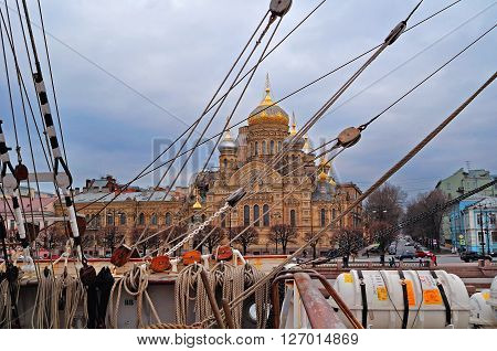 SAINT PETERSBURG, RUSSIA - MARCH 2 2014. View of the Assumption church at Vasilievsky Island through the rigging of the barque Sedov on the foreground. Spring St Petersburg architectural landscape.