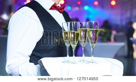 Waiter serving champagne on a tray at party