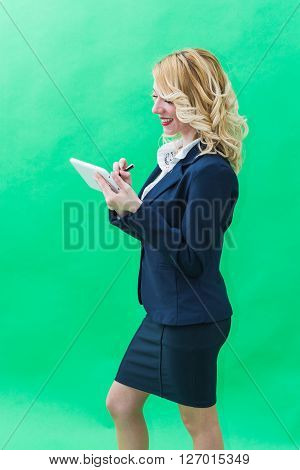 Young woman using tablet standing. Wearing blue suit she has blonde hair and blue or blue eyes on a white background.