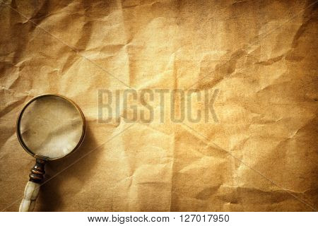 Vintage magnifying glass on old parchment paper background