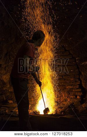 BIZKAIA, SPAIN - JULY 25, 2015: Blacksmith working in the fireplace of an old forge in Bizkaia, Spain on Jul 25, 2015