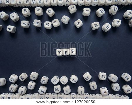 Word Yes Of Small White Cubes Next To A Bunch Of Other Letters On The Surface Of The Composition On