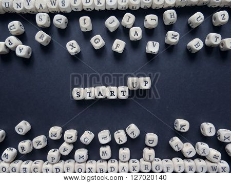 Word Start-up Of Small White Cubes Next To A Bunch Of Other Letters On The Surface Of The Compositio
