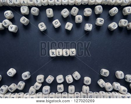 Word Risk Of Small White Cubes Next To A Bunch Of Other Letters On The Surface Of The Composition On