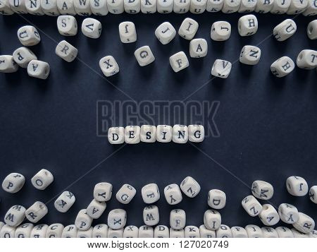 Word Desing Of Small White Cubes Next To A Bunch Of Other Letters On The Surface Of The Composition
