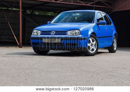 KRIVOY ROG, UKRAINE - APR 23- Blue Volkswagen Golf hatchback standing on a the asphalt in sunlight, Saturday 23 April 2016