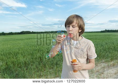 Portrait of Caucasian teenager boy standing with floating soap bubbles on dusty dirt farm field road