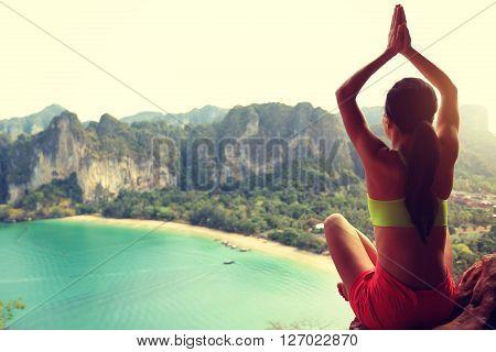 young healthy woman practice yoga on mountain peak rock