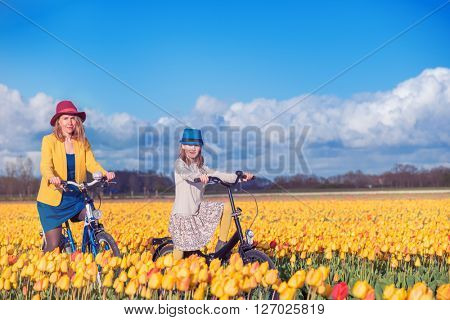 Smiling mother and daughter riding bikes through beautiful blooming tulip fields at the daylight