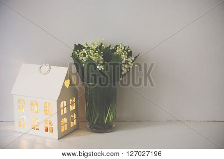 Simple home decoration, lilies of the valley in a vase on the shelf by the white wall background