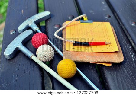 Mini golf equipment on the wooden bench