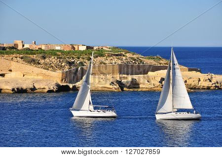 VALLETTA MALTA - FEBRUARY 16: Sail boats in the sea near Valletta on February 16 2014. Valletta is a capital and the largest city of Malta.