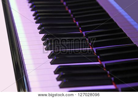Closeup of a modern piano keys with purple lighting and the reflection of the keys