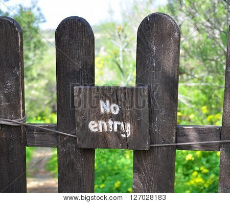 No entry sign on the wooden fence