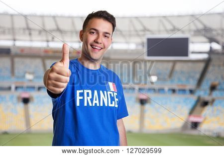 Happy french sports fan at stadium showing thumb up