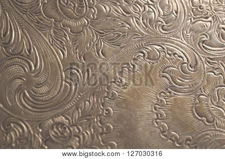 Closeup of tarnished antique silver with scrollwork carving and flowers.