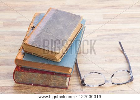Books stack and glasses on wooden table desktop